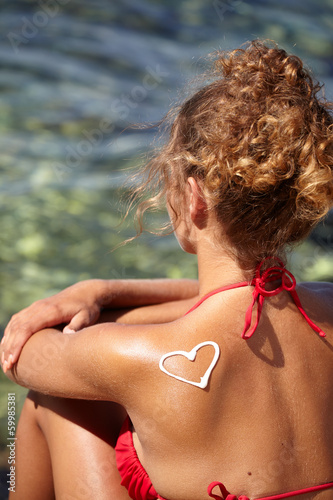 The heart of the cream on the female back on the beach