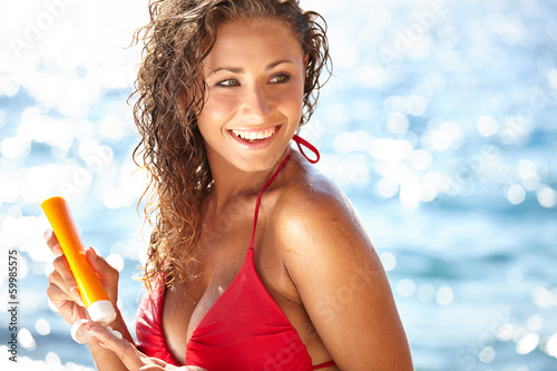 Sunscreen woman. Girl putting sun block on beach holding orange