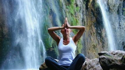 Woman meditating by the waterfall, Plitvice lakes, Croatia