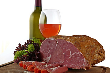 Smoked meat with wine and wine glass on wooden plate