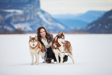 young girl playing with siberian husky dogs in winter park