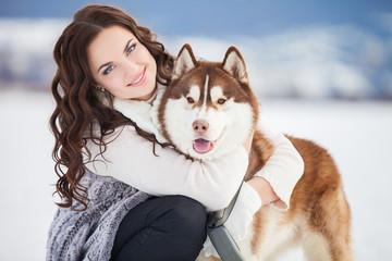 Girl embracing cute siberian husky in winter park