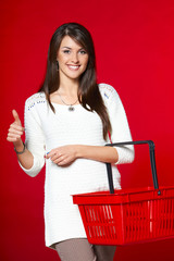 Woman with red shopping basket showing thumb up