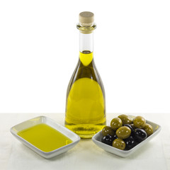 Olive oil in glass bottle and dish, and olives snack