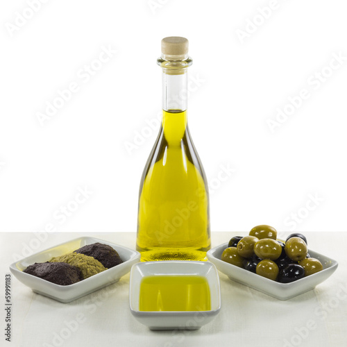 Olive oil in glass bottle and dished olive products