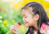 little girl with long dark hair sitting on poppy field