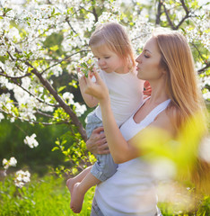 Happy mother and her little daughter in the spring