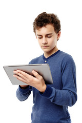 Smart teenager working on a tablet he is holding