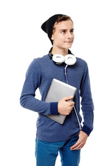 Trendy teenager with headphones around the neck and holding a ta