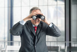Businessman using binoculars