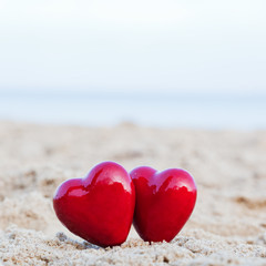 Two red hearts on the beach symbolizing love, Valentine's Day