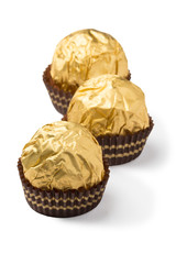 Three chocolate candies wrapped in golden foil isolated on white