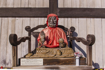 The wooden buddha with red coat at Todiaji temple, nara, japan