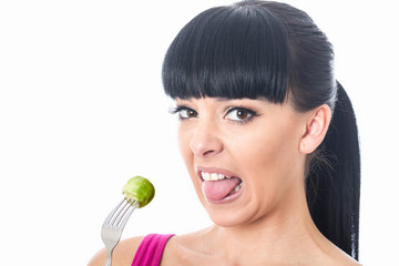 Young Woman Holding Brussel Sprout on a Fork