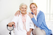 Frau umarmt alte Seniorin zu Hause