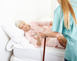 Krankenschwester hilft Seniorin beim Aufstehen