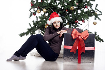 Young woman sitting near xmas tree with present