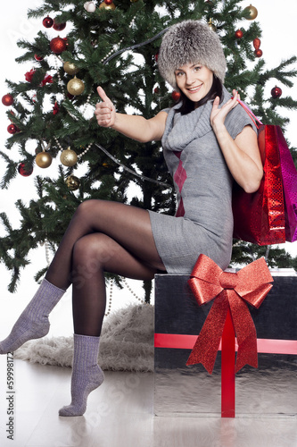 Young woman sitting near xmas tree with present after shopping d