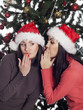 Two women near christmas tree gossip