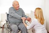 Frau hält Hände von Mann im Rollstuhl