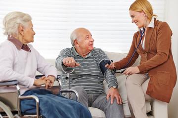 Frau misst Blutdruck bei ihren alten Eltern