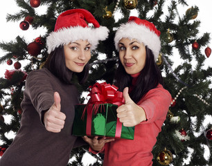 Two women near christmas tree with present showing hand ok sign