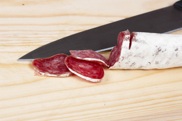 salami cut with a knife on a cutting board