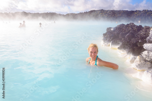 Beautiful young woman in Blue Lagoon geothermal spring , Iceland