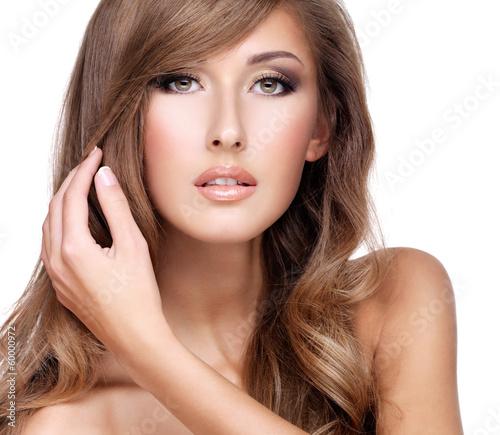 Closeup of a beautiful woman touching her gorgeous long hair