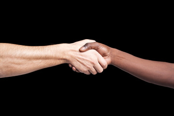 Handshake between african and a caucasian man against dark backg