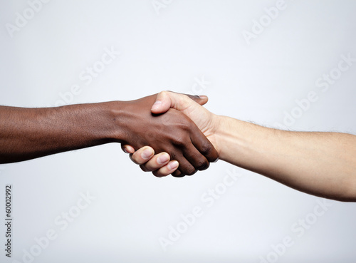 Handshake between african and a caucasian man over gray backgrou