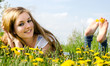Young blond woman enjoys the spring between dandelions