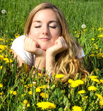 Young beautiful woman enjoys the spring between dandelions