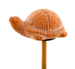 Tortoise in clay on wooden stick