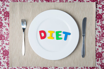 healthy food and diet concept - word DIET on a white plate