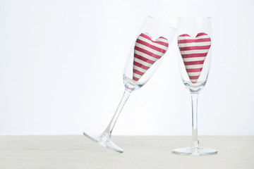 Valentine concept - two stripped hearts in champagne glasses