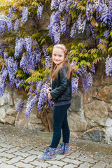 Spring portrait of a cute little girl, wisteria on background