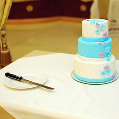 White and blue wedding cake on table