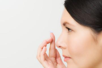 Frau setzt eine Kontaktlinse ein