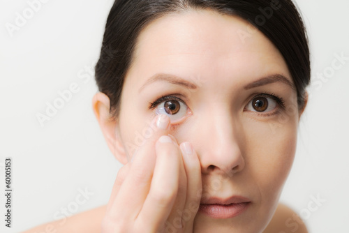 canvas print picture Frau setzt eine Kontaktlinse ein