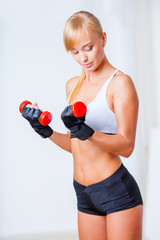 woman holding red dumbbells