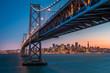 Leinwandbild Motiv San Francisco skyline framed by the Bay Bridge at sunset