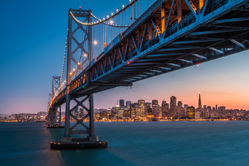 San Francisco skyline framed by the Bay Bridge at sunset