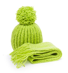 Green wool knitted scarf and hat on white background.