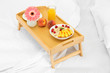 wooden tray with light breakfast on bed