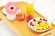 wooden tray with light breakfast on bed, close up