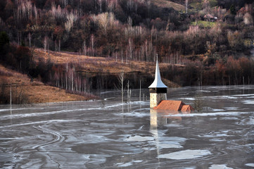 Abandoned church in a mud lake. Natural mining disaster with wat