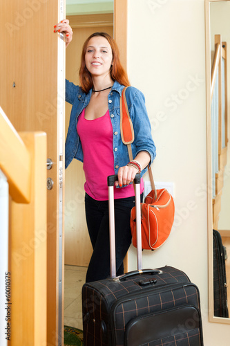 Positive woman with suitcase near door at home