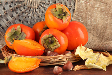 Ripe persimmons with nuts on table on wicker background
