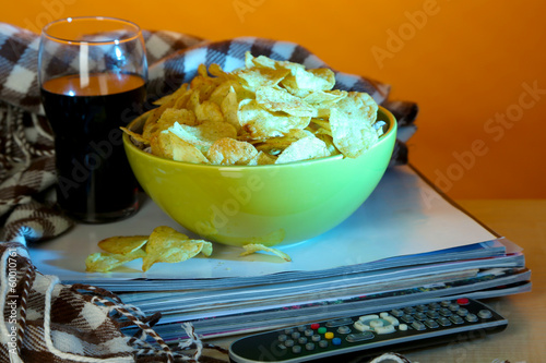 Chips in bowl, cola and TV remote
